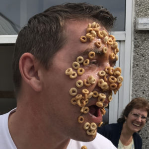 Adult playing game with cheerio breakfast cereal stuck on face