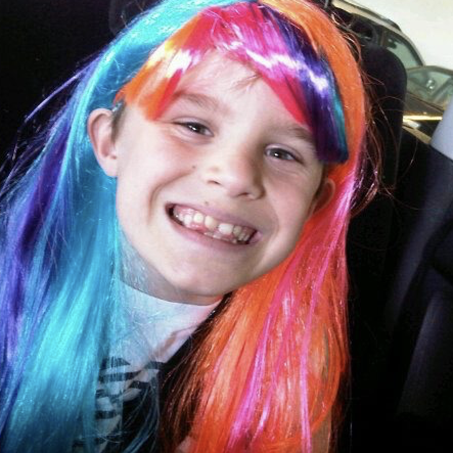 boy wearing a colourful wig smiling at the camera