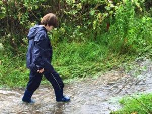 Child walking through stream