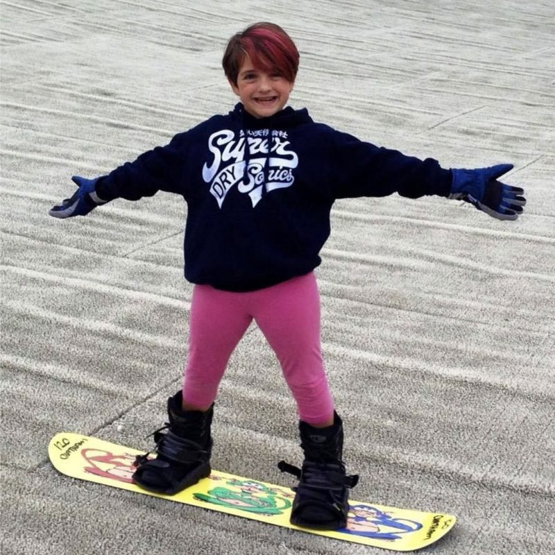 Girl on snowboard smiing at camera