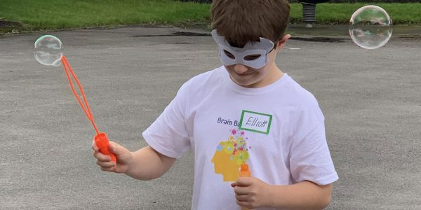 boy in mask playing with bubbles